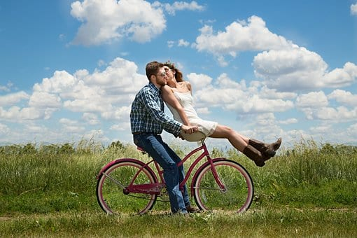 Woman and man cycling happily through the countryside