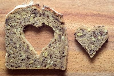 Slice of brown bread with a heart cut out of the middle and placed next to the bread