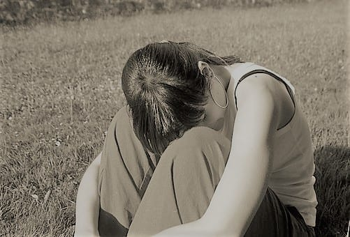 Woman sitting crouched over in pain in a field, with the image in sepia